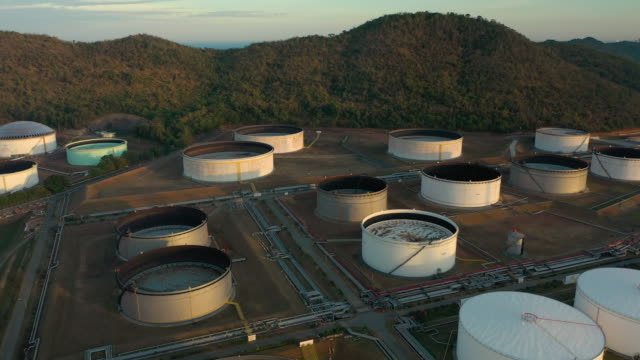 vídeos de stock, filmes e b-roll de dolly deixou de petróleo e tanque de gás no tempo do pôr do sol - oleoduto