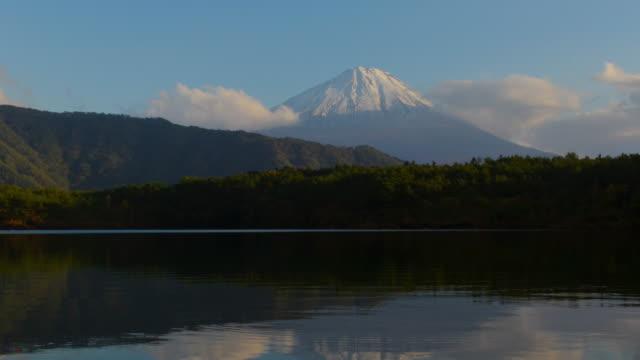 澄んだ青い空と時間経過 4 k 山富士と湖彩で小さな雲緑丘を右に左にドリー中部地方山梨県 - 山梨県点の映像素材/bロール