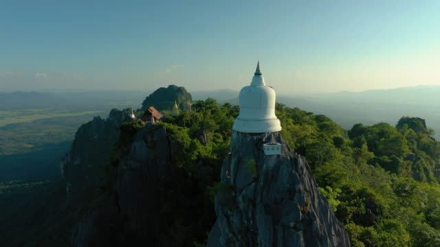dolly left: white pagoda on mountain peak in aerial view shot - buddha video stock e b–roll