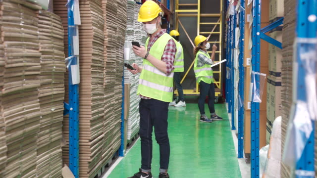 4k uhd dolly left: working of group of warehouse interracial team work on inventory in distribution center. they wear protective face mask to reduce risk of coronavirus covid-19 infection. business inventory and industry concept. - postal worker stock videos & royalty-free footage