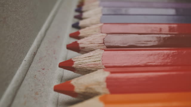dolly macro shot of colored pencils in a row background - pencils in a row stock videos & royalty-free footage