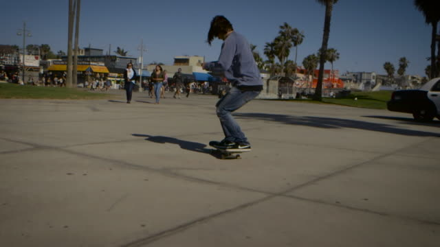 dolly of skater filming himself doing an ollie venice california skatepark - un ragazzo adolescente video stock e b–roll