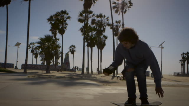 dolly of skater filming himself with phone in venice california skatepark - un ragazzo adolescente video stock e b–roll