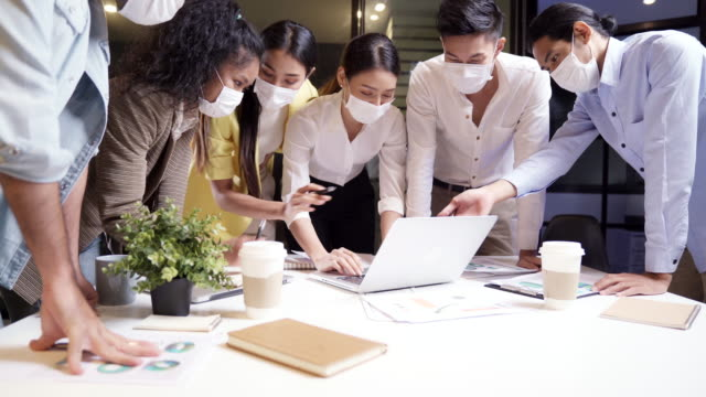 4k uhd dolly out : work late concept of interracial asian business team brainstorm idea at office meeting room at night. they wear face mask reduce risk to infection of covid-19 coronavirus as new normal lifestyle. - brainstorming stock videos & royalty-free footage