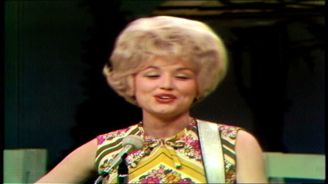 "dolly parton performs ""dumb blonde"" . porter wagoner briefly steps into frame to say something into parton's ear. parton sings and plays acoustic... - television show stock-videos und b-roll-filmmaterial"
