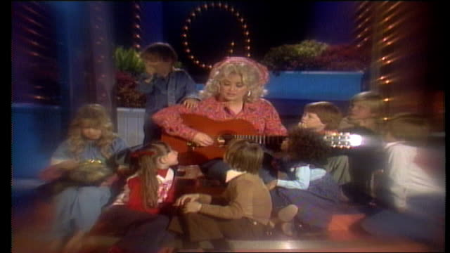 dolly parton seated on stage surrounded by a group of young caucasian and african-american boys and girls / dolly tells the children she was raised... - television show stock videos & royalty-free footage