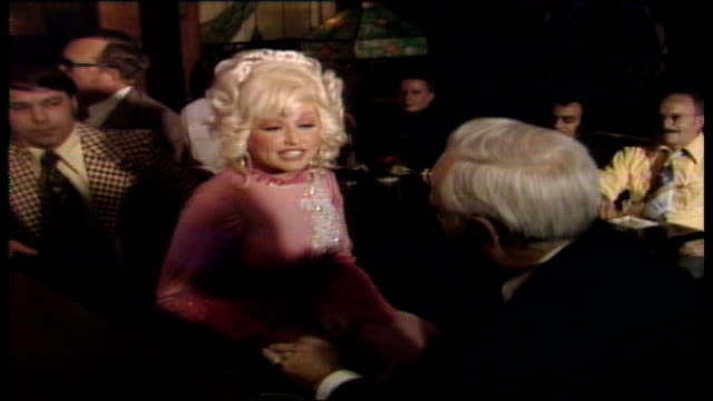 vídeos de stock e filmes b-roll de dolly parton talks about live music venues in nashville, brass rail interior in bg, fireplace and pictures hanging on a wall / parton enters the... - television show