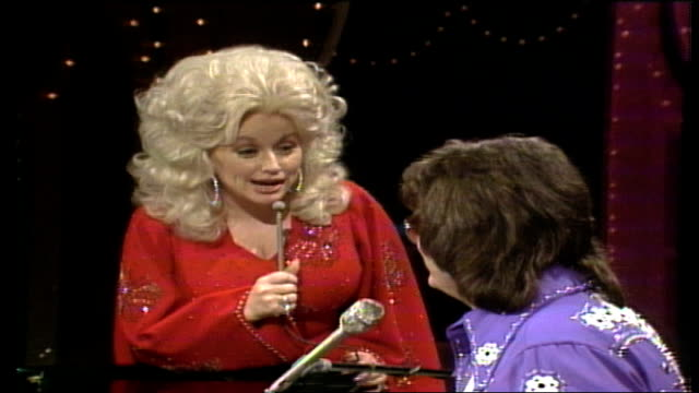 dolly parton wearing red jumpsuit with butterfly sequins and ronnie milsap wearing blue collared shirt with floral sequins engage in playful banter... - jumpsuit stock videos and b-roll footage