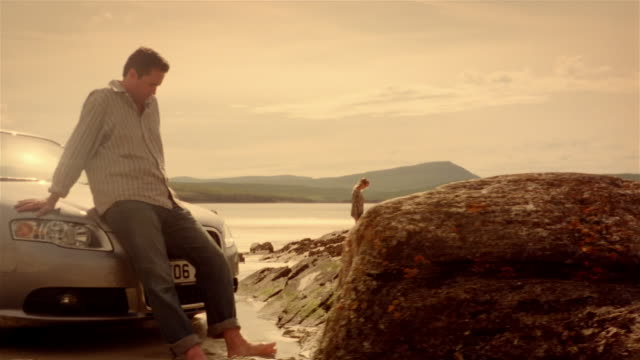 dolly past man leaning against convertible car parked on rocky shore and woman walking around in background to rocks - schottland stock-videos und b-roll-filmmaterial