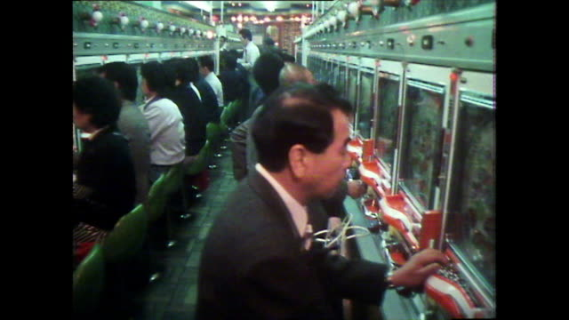 dolly past rows of japanese men playing pachinko; 1981 - leisure games stock videos & royalty-free footage