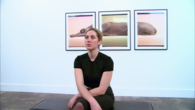 Dolly past woman sitting on bench at gallery opening and looking at artwork across room / man walking up to and looking at three-panel print of a Weimaraner by William Wegman on wall behind woman