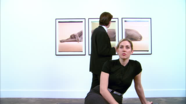 vídeos de stock e filmes b-roll de dolly past woman sitting on bench at gallery opening and looking at artwork across room / man looking at three-panel print of a weimaraner by william wegman on wall behind woman - dolly shot