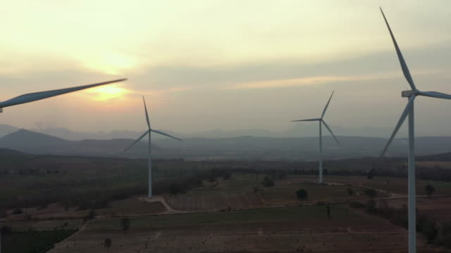 vídeos de stock e filmes b-roll de dolly right aerial view of wind turbine in sunset time - grupo grande de objetos