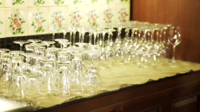 vídeos de stock e filmes b-roll de ms dolly right camera of clear glasses upside down on the bar counter. - copo vazio