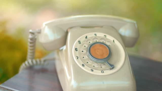 木製のテーブルの上にヴィンテージ電話のcuドリー右カメラ。 - 加入電話点の映像素材/bロール