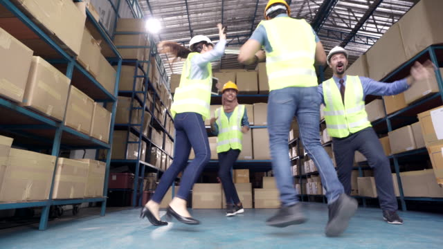 4k uhd dolly right: interracial team of warehouse worker and manager celebrate after finish working . using in business warehouse and celebration concept. - oregon coast stock videos & royalty-free footage