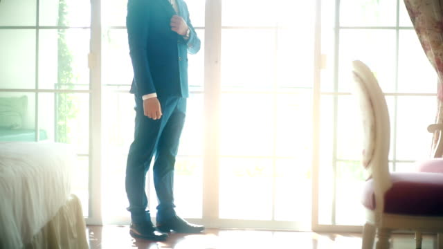 MS Dolly right : Luxury groom in blue suit standing in the room against soft bright background.