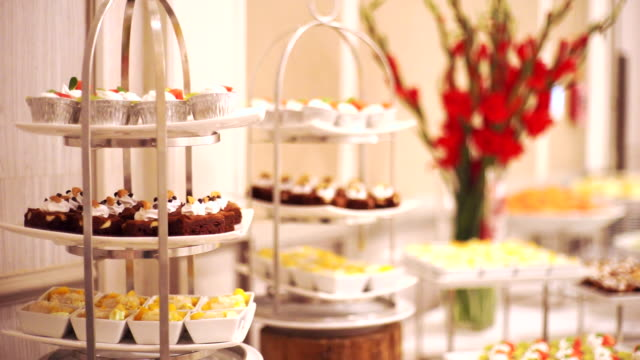 ms dolly right of dessert stands of different dessert on the wedding buffet. - sweet food stock videos & royalty-free footage