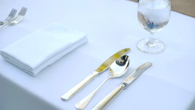 ms dolly right of table setting with cutlery, napkin and glass on the table. - tablecloth stock videos & royalty-free footage