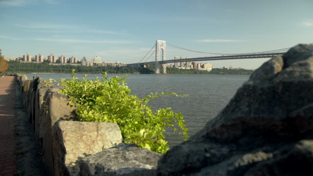 dolly right shot of george washington bridge with rocks in the foreground - hudson river stock videos & royalty-free footage