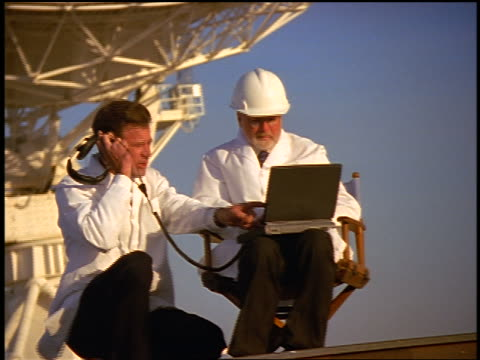 dolly shot 2 male scientists with laptop + headphones in front of vla radio telescope dishes / new mexico - hand sign stock videos & royalty-free footage