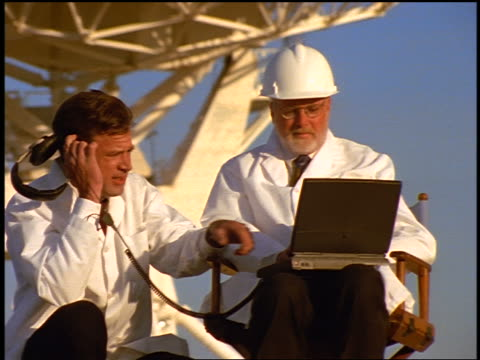 vídeos de stock, filmes e b-roll de dolly shot 2 male scientists with laptop + headphones in front of vla radio telescope dishes / new mexico - 1990 1999