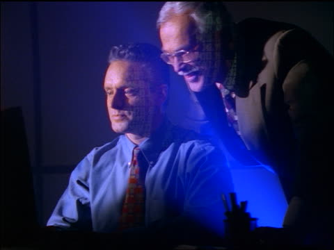 dolly shot 2 middle-aged businessmen using computer + smiling / reflection of computer screen on their faces - employee engagement stock videos & royalty-free footage
