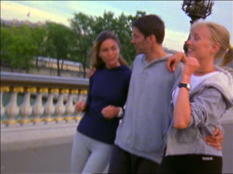 dolly shot 3 young adults (1 man) walking together talking + smiling on pont alexandre iii / paris, france - femmina con gruppo di maschi video stock e b–roll