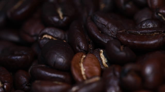 dolly shot: 4k close-up of coffee beans in motion - coffee drink stock videos & royalty-free footage