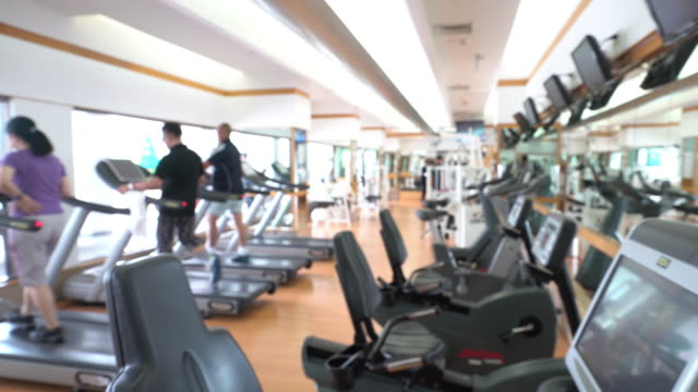dolly shot: abstract blurred background: fitness center gym club - exercise equipment stock videos and b-roll footage