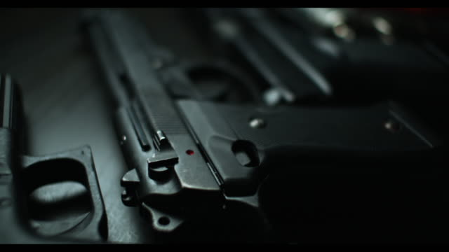 dolly shot across a row of pistols and revolvers - arma da fuoco video stock e b–roll