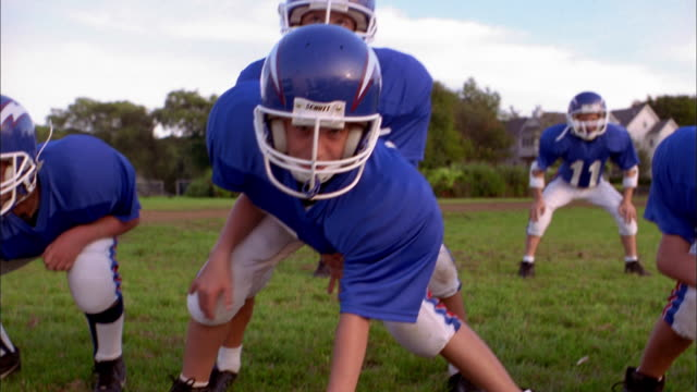 Dolly shot across group of young football players in offensive line formation
