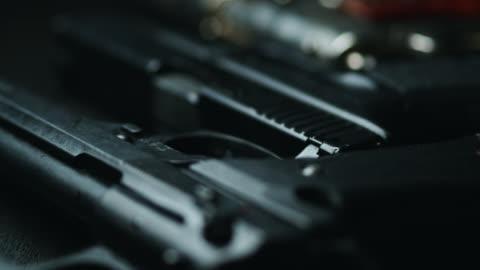 dolly shot across variety of handguns - handgun stock videos & royalty-free footage