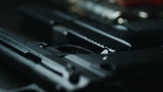 stockvideo's en b-roll-footage met dolly shot across variety of handguns - criminaliteit