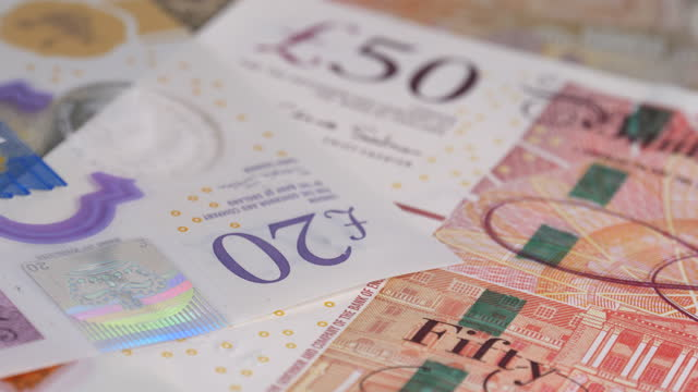 dolly shot across various uk bank notes - winning stock videos & royalty-free footage