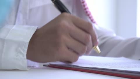 dolly sköt arabisk man som arbetar med dokument - överenskommelse bildbanksvideor och videomaterial från bakom kulisserna