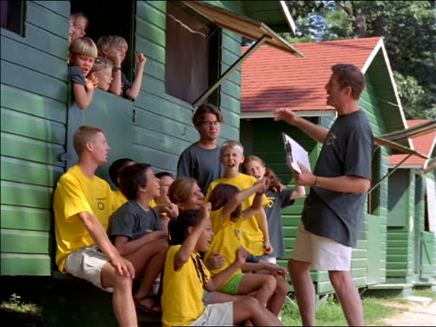 dolly shot around male camp counselor cheering on group of children outside green cabin - summer camp helper stock videos & royalty-free footage