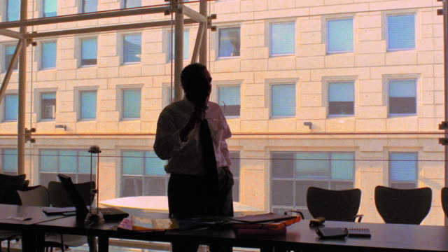 dolly shot around silhouette of businessman standing behind desk looking out window / pacing behind desk - loneliness stock videos and b-roll footage