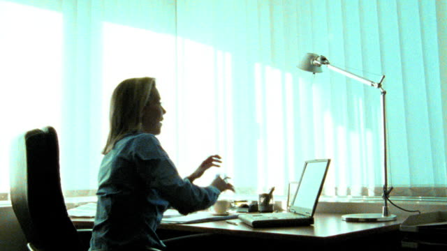 dolly shot around silhouette of businesswoman typing on laptop on desk / leaning back + stretching arms out