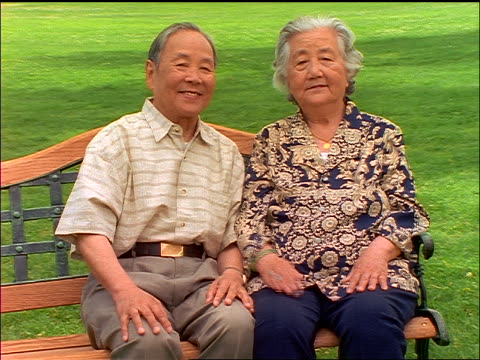 dolly shot around smiling Chinese senior couple holding hands + sitting on bench outdoors