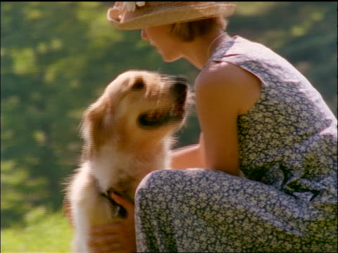 dolly shot around woman wearing straw hat kneeling outdoors + cuddling with golden retriever - straw hat stock videos & royalty-free footage