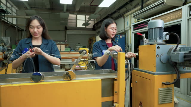 dolly shot: asian engineer working on polymer production line to produce polymer extrud  by using twin-screw extruder. woman engineering, scientist student wearing blue clothe doing polymer experiments, discussing with friends. concept of woman in stem - manufacturing machinery stock videos & royalty-free footage