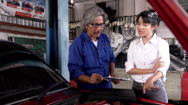 dolly shot: asian young female manager feel displeased how to senior car mechanic work - customer stock videos & royalty-free footage