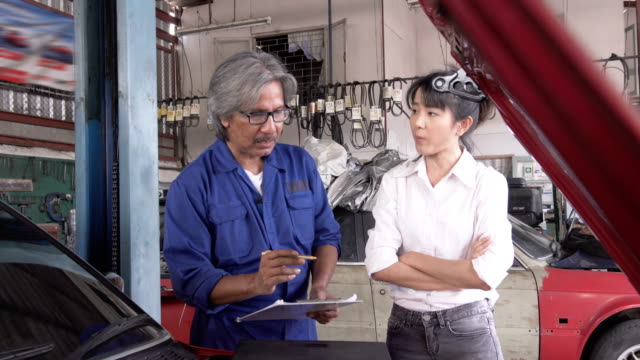 dolly shot: asian young female manager feel displeased senior car mechanic work - customer stock videos & royalty-free footage