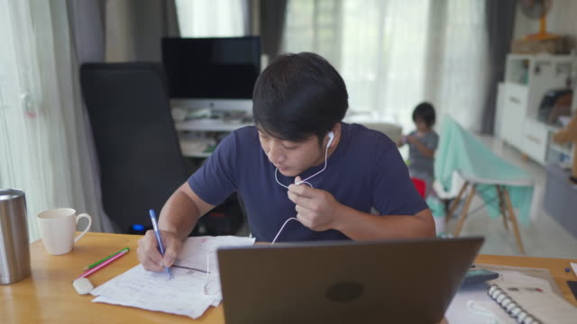 dolly shot asian young man working from home with small child playing in background - two generation family stock videos & royalty-free footage