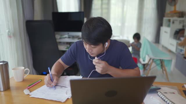 vídeos y material grabado en eventos de stock de dolly disparó a un joven asiático que trabajaba desde casa con un niño pequeño jugando en segundo plano - adulto de mediana edad