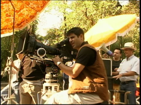 dolly shot away from and toward director, cameraman + crew on film set outdoors / mexico city - film director stock videos and b-roll footage