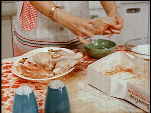 vídeos y material grabado en eventos de stock de 1950 dolly shot away from close up woman removing chicken pieces from box + preparing them for cooking in kitchen - diez segundos o más