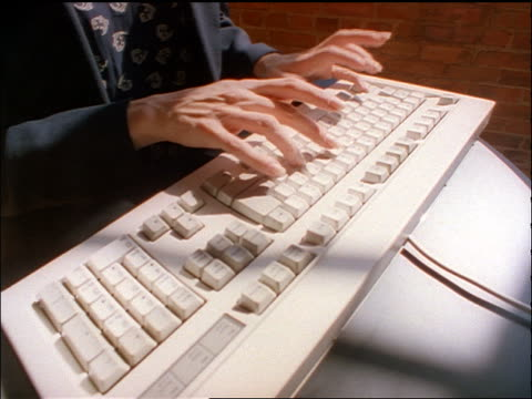 stockvideo's en b-roll-footage met dolly shot away from close up woman's hands typing on computer keyboard to long shot woman using computer in empty room - 1998