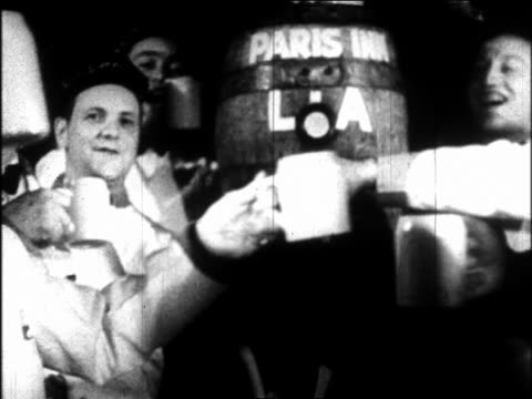 B/W 1933 dolly shot away from men pouring beer into mugs from barrel toasting / repeal of Prohibition